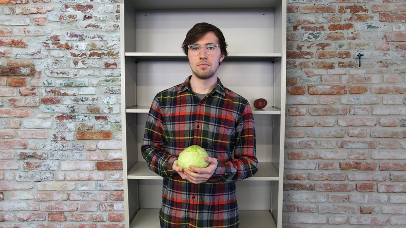 A man holding a cabbage.