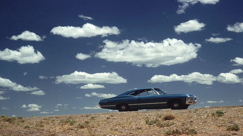 A blue car on the highway in the 70's.